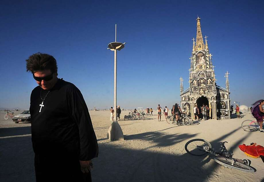 "A man in a priest outfit walks away from the ""Photo Chapel"" at the Burning Man festival in Gerlach, Nev. on Friday, Aug. 30, 2013. Once a year, tens of thousands of participants gather in Nevada's Black Rock Desert for the counterculture event. Photo: Andy Barron, Associated Press"