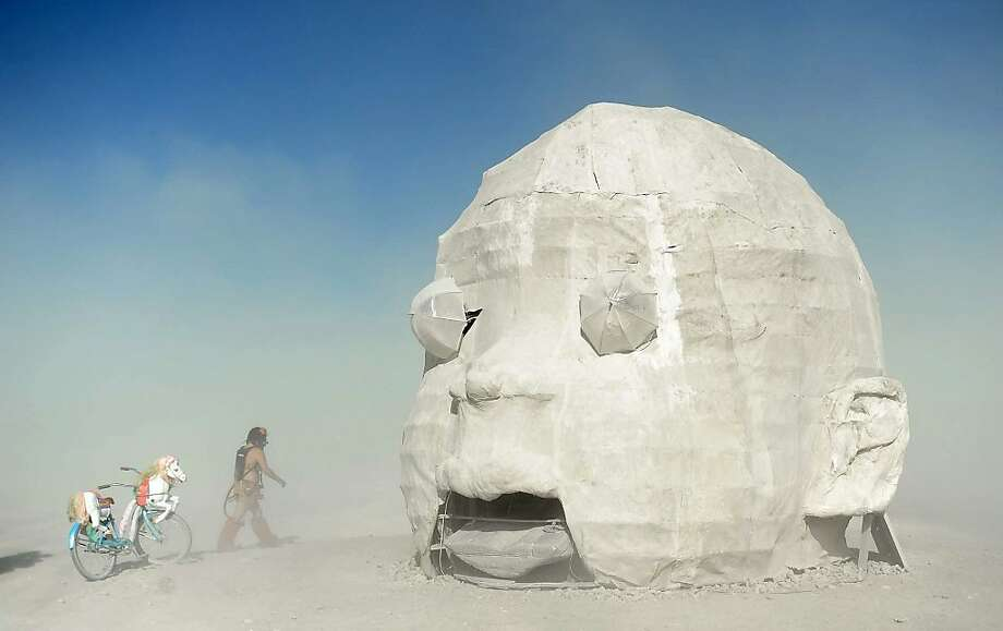 "In this Thursday, Aug. 19, 2013 photo, Sam Ray visits the ""Baby Head"" art piece at Burning Man in Gerlach, Nev. Once a year, tens of thousands of participants gather for Burning Man in Nevada's Black Rock Desert to create Black Rock City, dedicated to community, art, self-expression and self-reliance. Photo: Andy Barron, Associated Press"