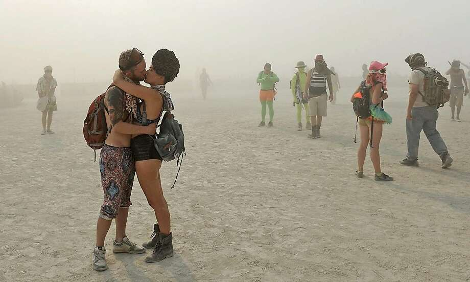 In this Wednesday, Aug. 28, 2013 photo, a couple kisses at Burning Man in Gerlach, Nev. Once a year, tens of thousands of participants gather in Nevada's Black Rock Desert to create Black Rock City, dedicated to community, art, self-expression and self-reliance. Photo: Andy Barron, Associated Press