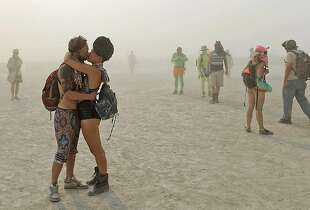 In this Wednesday, Aug. 28, 2013 photo, a couple kisses at Burning Man in Gerlach, Nev. Once a year, tens of thousands of participants gather in Nevada's Black Rock Desert to create Black Rock City, dedicated to community, art, self-expression and self-reliance. (AP Photo/The Reno Gazette-Journal, Andy Barron)