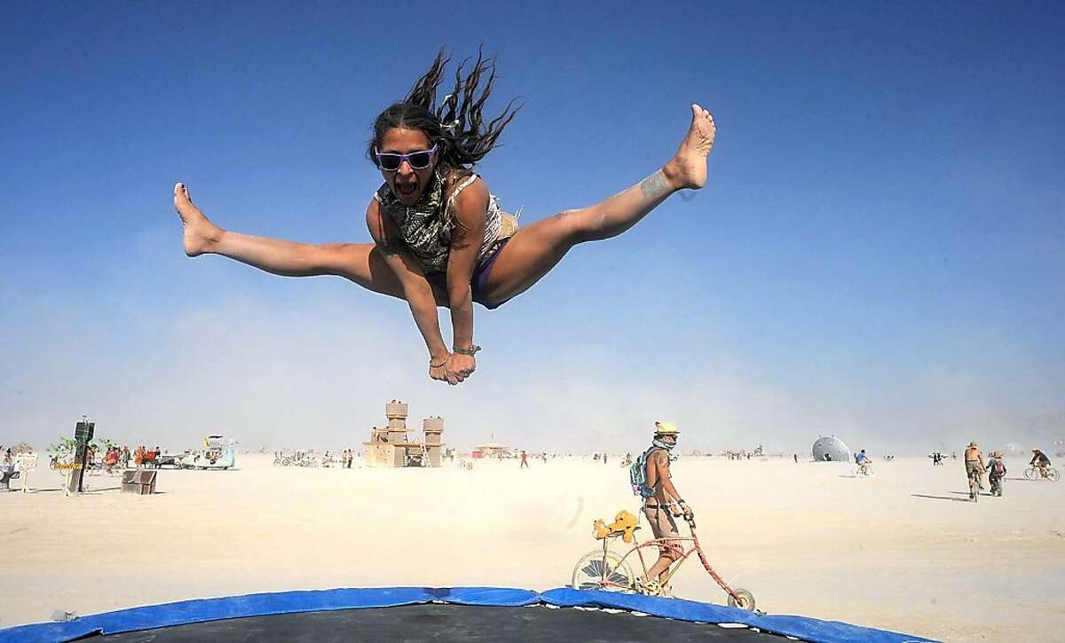 In this Aug. 29, 2013 photo, Selam Borges plays on a trampoline at Burning Man in Gerlach, Nev.