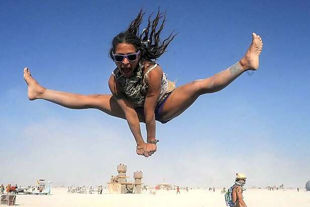 In this Aug. 29, 2013 photo, Selam Borges plays on a trampoline at Burning Man in Gerlach, Nev. Once a year, tens of thousands of participants gather for Burning Man in Nevada's Black Rock Desert to create Black Rock City, dedicated to community, art, self-expression and self-reliance. (AP Photo/The Reno Gazette-Journal, Andy Barron)