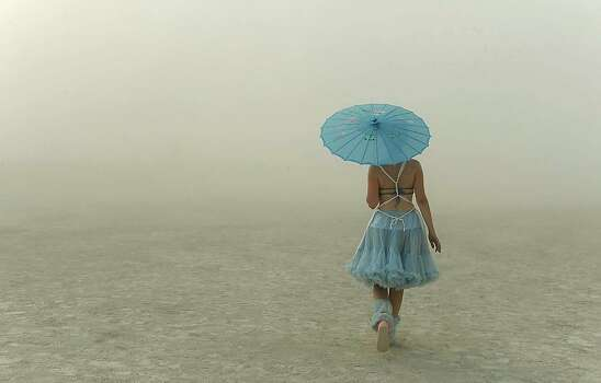 A young woman walks through the dusty playa at Burning Man in 2013. Photo: Andy Barron, Associated Press