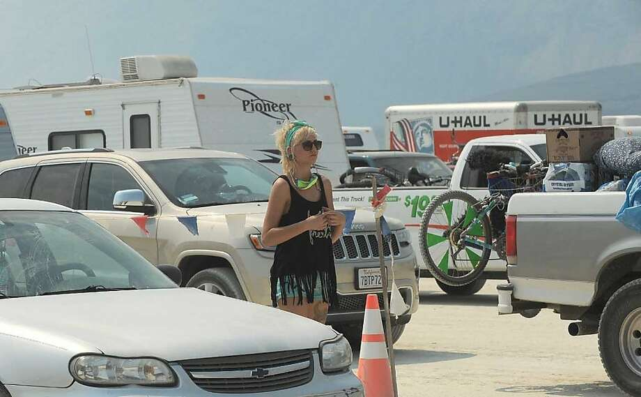 "In this Aug. 26, 2013 photo, a woman looks out at cars waiting to enter ""Burning Man,"" an annual arts festival, in Gerlach, Nev. According to The Reno Gazette-Journal an estimated 68,000 people are anticipated to attend the event. Photo: Andy Barron, Associated Press"