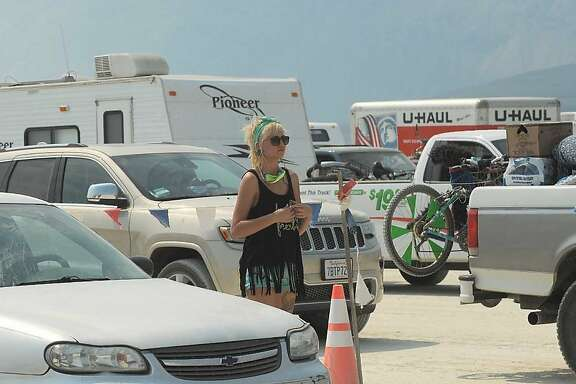 "In this Aug. 26, 2013 photo, a woman looks out at cars waiting to enter ""Burning Man,"" an annual arts festival, in Gerlach, Nev. According to The Reno Gazette-Journal an estimated 68,000 people are anticipated to attend the event. (AP Photo/Reno Gazette-Journal, Andy Barron)"