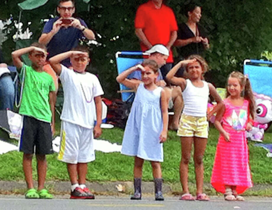 Young children salute the marchers at the 52nd annual Labor Day parade in Newtown, Conn. on Monday Sept. 2, 2013. Photo: Brian Koonz / The News-Times
