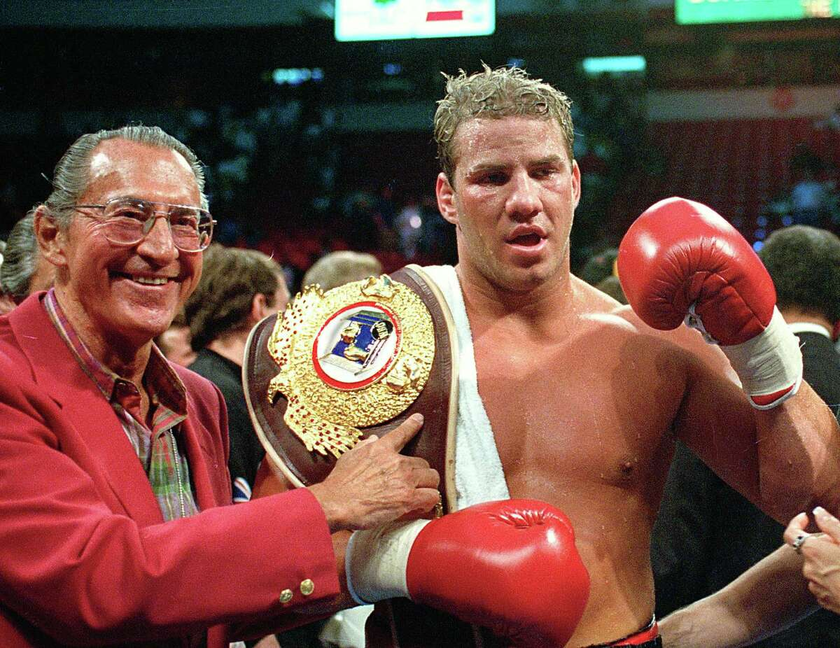 In this June 7, 1993 file photo, newly crowned WBO heavyweight champion Tommy Morrison receives his championship belt after defeating George Foreman in Las Vegas, Nev.