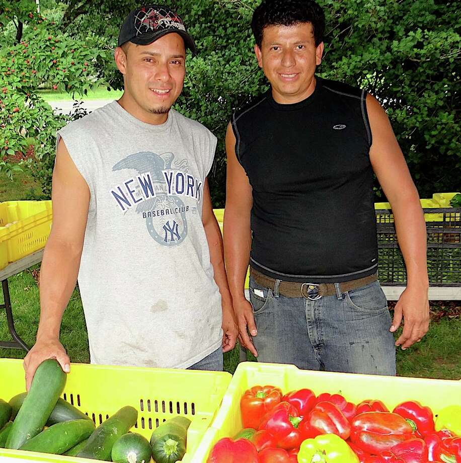 Hector Morales and Oscar Gudiel of Vaszauskas Farm in Middlebury offer fresh peppers, potatoes, onions and greens at the Greenfield Hill Farmers' Market on Saturday. Photo: Mike Lauterborn / Fairfield Citizen contributed