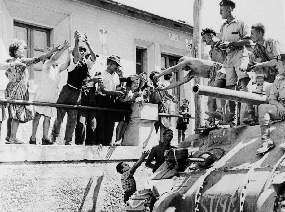 The inhabitants of Reggio cheer the arrival of an Allied tank during the Allies' invasion of Italy, September 1943. Photo: Keystone, Getty Images / 2006 Getty Images