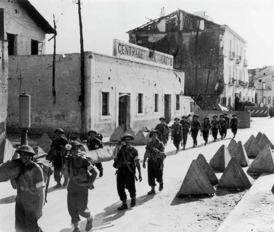 British infantry soldiers march past a road block in the Italian port of Salerno, Italy, during World War II, September 1943. Photo: Keystone, Getty Images / 2004 Getty Images