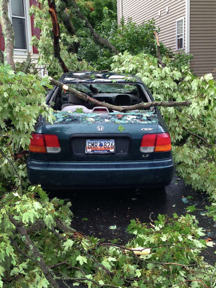 A large tree limb fell onto a car in a driveway on Balmforth Ave. during a heavy downpour in Danbury, Conn. on Monday Sept. 2, 2013. A quick passing storm came through the area about 10:30 a.m. Photo: Terri Rousseau / The News-Times
