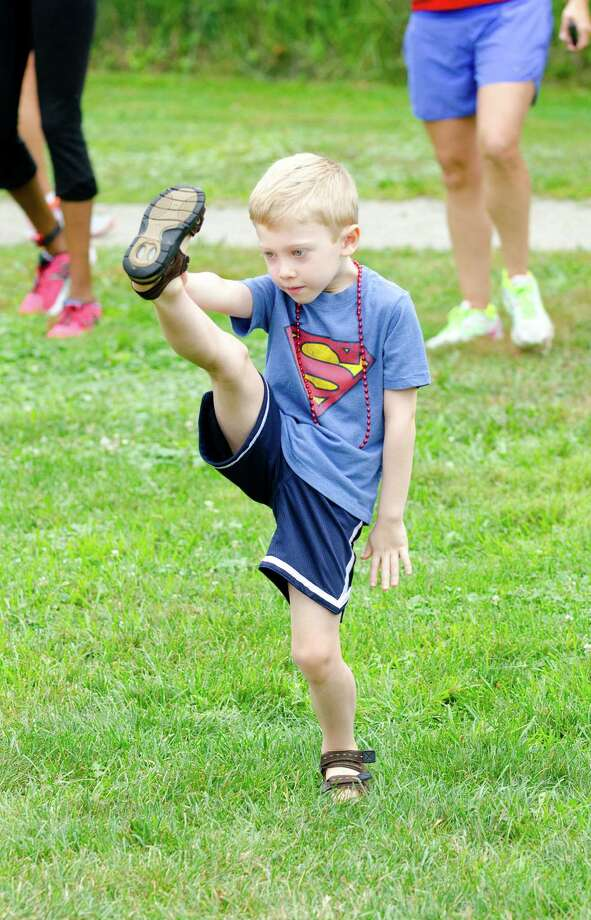 Leo Field, 7, of Stamford, warms up during the sixth annual 5k Run/Walk and Family Fun Day to benefit JumpStart at the Stamford Jewish Community Center (JCC) on Newfield Avenue in Stamford on Monday, Sept. 2, 2013. Photo: Amy Mortensen / Connecticut Post Freelance