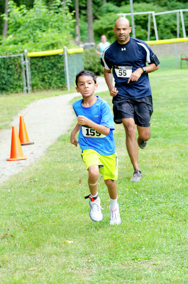 Roahn Sarma, 8, and his father, Ram Sarma, of Stamford, cross the finish line together during the sixth annual 5k Run/Walk and Family Fun Day to benefit JumpStart at the Stamford Jewish Community Center (JCC) on Newfield Avenue in Stamford on Monday, Sept. 2, 2013. Photo: Amy Mortensen / Connecticut Post Freelance