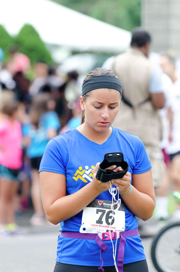 Kimberly Loop sets her iPod during the sixth annual 5k Run/Walk and Family Fun Day to benefit JumpStart at the Stamford Jewish Community Center (JCC) on Newfield Avenue in Stamford on Monday, Sept. 2, 2013. Photo: Amy Mortensen / Connecticut Post Freelance