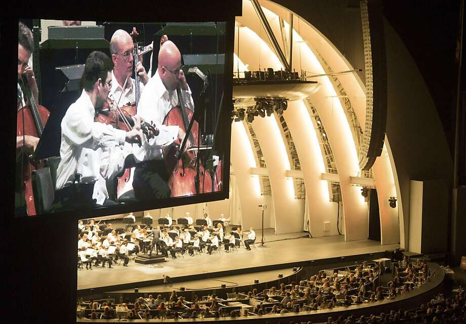 An orchestra is displayed on a large high-definition video screen at the Hollywood Bowl in Los Angeles. Photo: J. Emilio Flores, New York Times