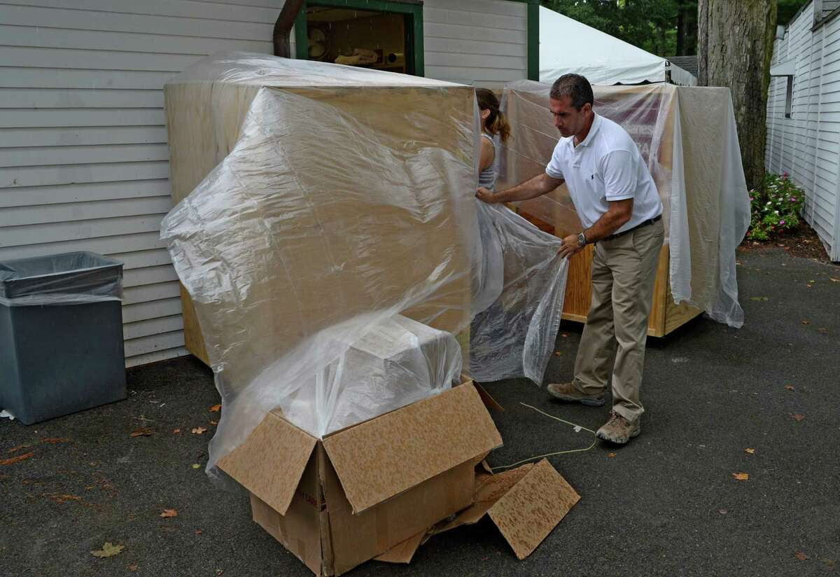 Track photographer Adam Coglianese covers his shipping cases to protect them from the rain as the 150th meeting comes to a close Sept. 2, 2013, at the Saratoga Race Course in Saratoga Springs, N.Y. (Skip Dickstein/Times Union)