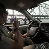 Highway Patrol officer Daniel Hill waves to fellow officers patrolling on the new eastern Bay Bridge span where construction crews are finishing up their work in Oakland, Calif. on Monday, Sept. 2, 2013. Caltrans expects to open the bridge to commuters on Tuesday at 5 a.m., but may possibly open it several hours earlier if work is completed ahead of schedule.