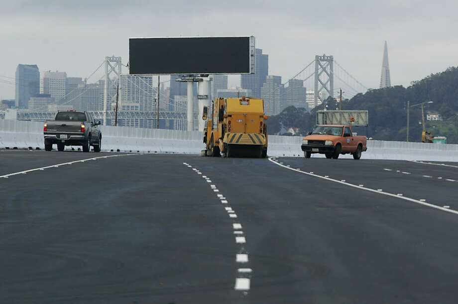 A sweeper cleans up leftover debris on westbound lanes as construction crews are wrap-up work on the new eastern span of the Bay Bridge in Oakland, Calif. on Monday, Sept. 2, 2013. Caltrans expects to open the bridge to commuters on Tuesday at 5 a.m., but may possibly open it several hours earlier if work is completed ahead of schedule. Photo: Paul Chinn, The Chronicle