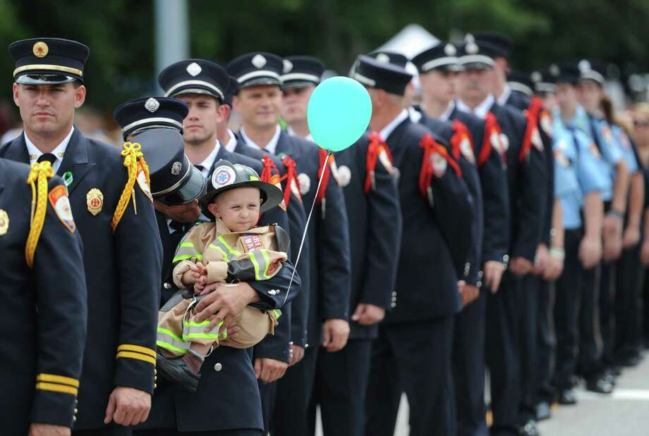 "Archie Paloian, of the Sandy Hook Volunteer Fire & Rescue Company, carries one of the crew members' nephew, Charlie Jeltema, 2, of Sandy Hook, in the 52nd Annual Newtown Labor Day Parade in Newtown, Conn. on Monday, Sept. 2, 2013.  About 100 floats and groups participated in the parade, themed ""We are Newtown - marching strong."" Photo: Tyler Sizemore / The News-Times"