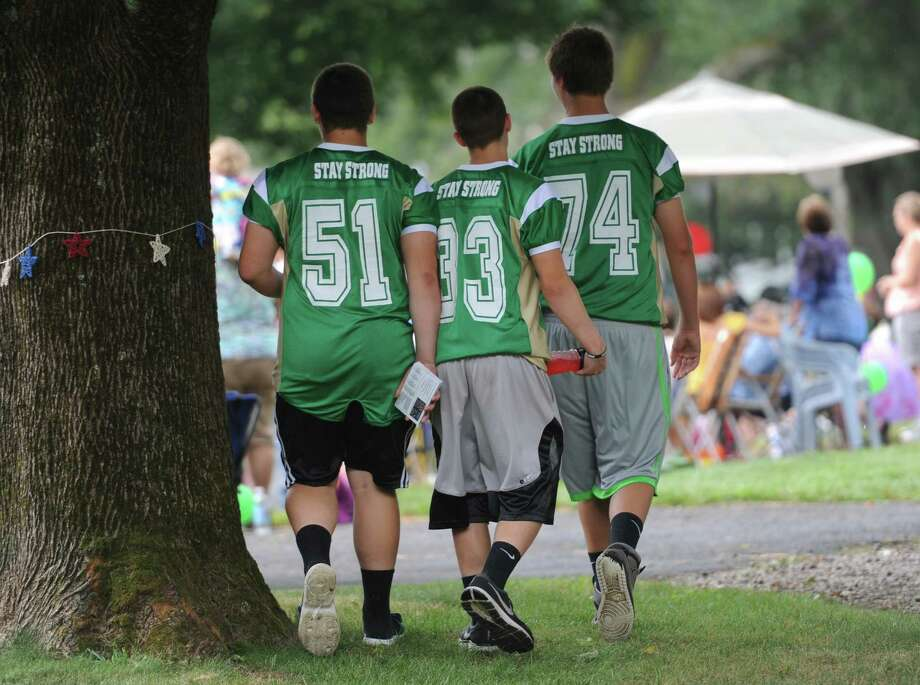 "Newtown football players wearing green Sandy Hook ""stay strong"" jerseys walk alongside the parade route during the 52nd Annual Newtown Labor Day Parade in Newtown, Conn. on Monday, Sept. 2, 2013.  About 100 floats and groups participated in the parade, themed ""We are Newtown - marching strong."" Photo: Tyler Sizemore / The News-Times"