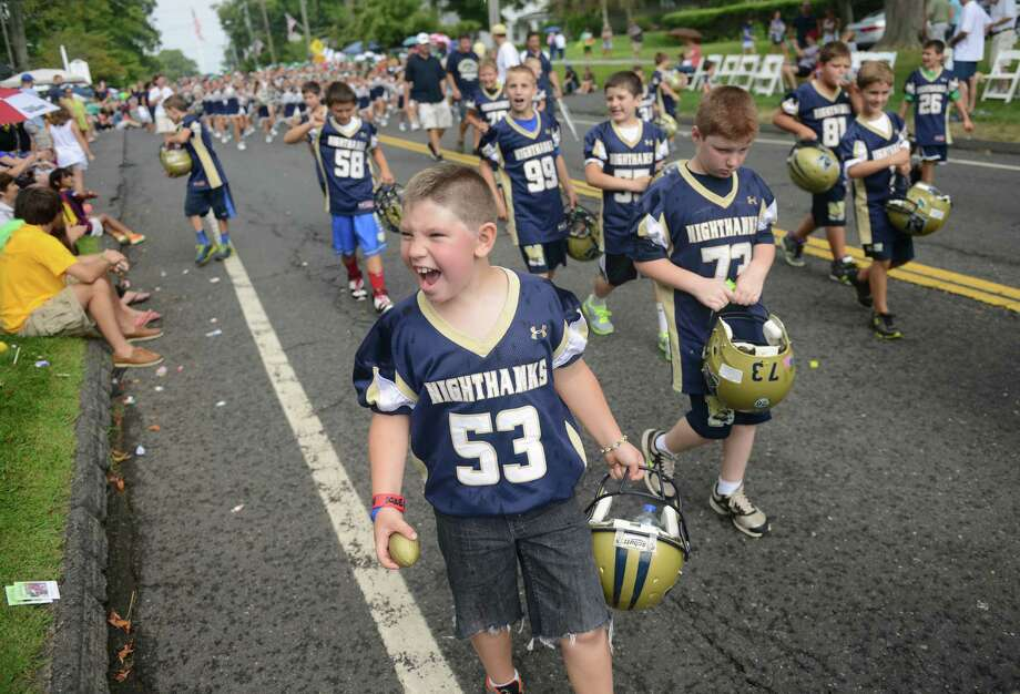 "Newtown football players march in the 52nd Annual Newtown Labor Day Parade in Newtown, Conn. on Monday, Sept. 2, 2013.  About 100 floats and groups participated in the parade, themed ""We are Newtown - marching strong."" Photo: Tyler Sizemore / The News-Times"