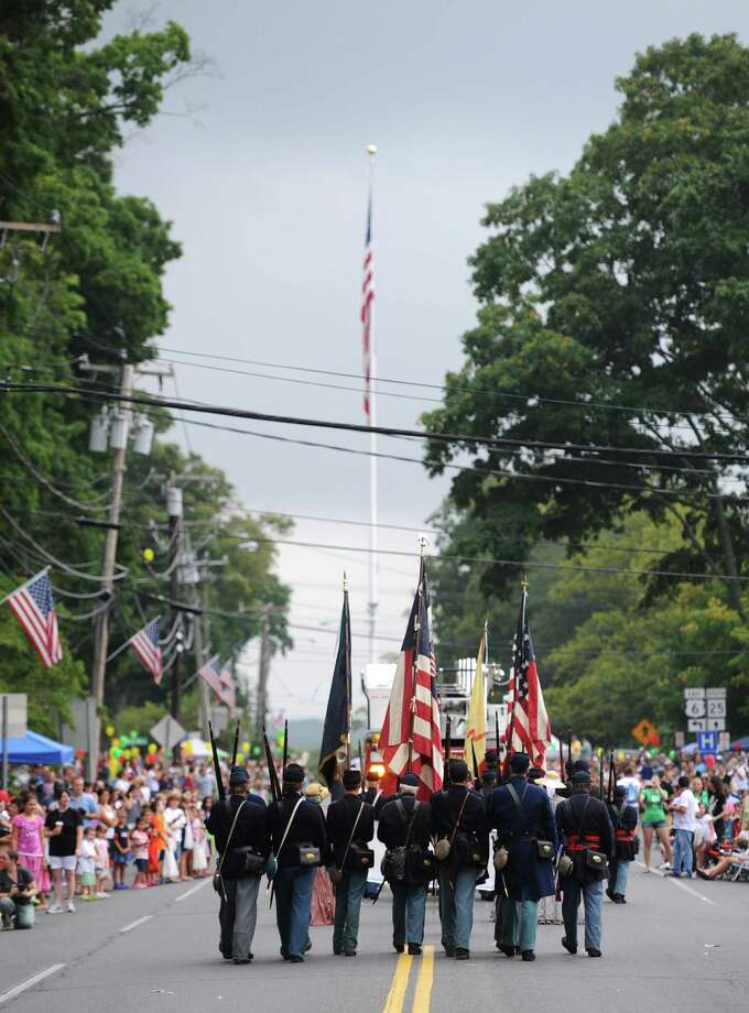 "The Connecticut 11th Regimant Infantry re-enactors walk toward the flagpole while marching in the 52nd Annual Newtown Labor Day Parade in Newtown, Conn. on Monday, Sept. 2, 2013.  About 100 floats and groups participated in the parade, themed ""We are Newtown - marching strong."" Photo: Tyler Sizemore / The News-Times"