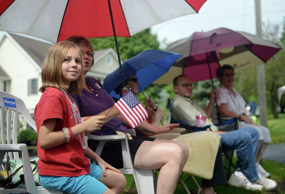 "Renata Boulay, 8, of Plainville, takes cover under an umbrella at the 52nd Annual Newtown Labor Day Parade in Newtown, Conn. on Monday, Sept. 2, 2013.  About 100 floats and groups participated in the parade, themed ""We are Newtown - marching strong."" Photo: Tyler Sizemore / The News-Times"