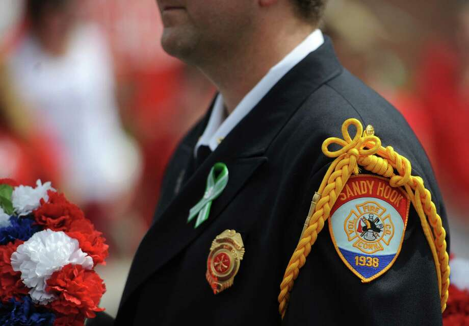 """A member of the Sandy Hook Volunteer Fire & Rescue Company marches in the 52nd Annual Newtown Labor Day Parade in Newtown, Conn. on Monday, Sept. 2, 2013.  About 100 floats and groups participated in the parade, themed """"We are Newtown - marching strong."""" Photo: Tyler Sizemore / The News-Times"""