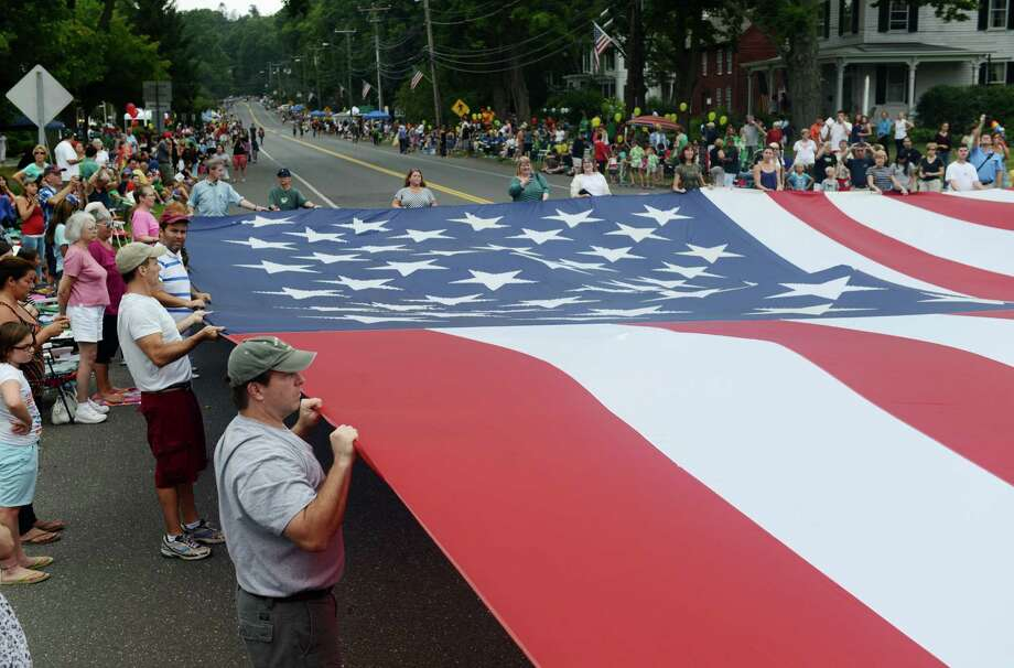 "Volunteers hold up a 90 foot long American flag before the start of the 52nd Annual Newtown Labor Day Parade in Newtown, Conn. on Monday, Sept. 2, 2013.  About 100 floats and groups participated in the parade, themed ""We are Newtown - marching strong."" Photo: Tyler Sizemore / The News-Times"