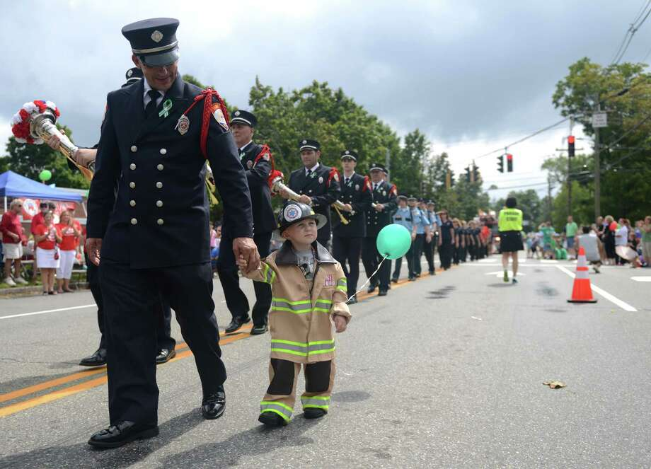 "Archie Paloian, of the Sandy Hook Volunteer Fire & Rescue Company, walks with one of the crew members' nephew, Charlie Jeltema, 2, of Sandy Hook, in the 52nd Annual Newtown Labor Day Parade in Newtown, Conn. on Monday, Sept. 2, 2013.  About 100 floats and groups participated in the parade, themed ""We are Newtown - marching strong."" Photo: Tyler Sizemore / The News-Times"
