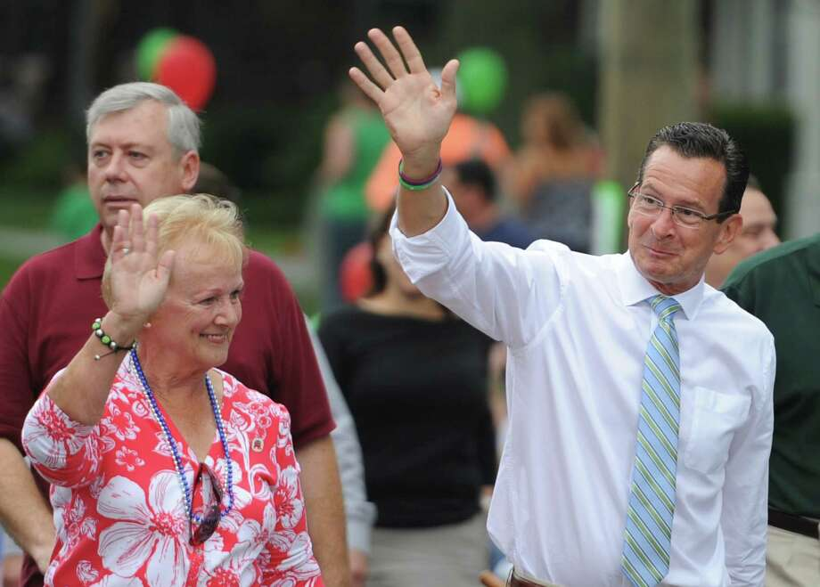 "Connecticut Gov. Dannel P. Malloy, right, waves to the crowd with Newtown First Selectman Pat Llodra while marching in the 52nd Annual Newtown Labor Day Parade in Newtown, Conn. on Monday, Sept. 2, 2013.  About 100 floats and groups participated in the parade, themed ""We are Newtown - marching strong."" Photo: Tyler Sizemore / The News-Times"