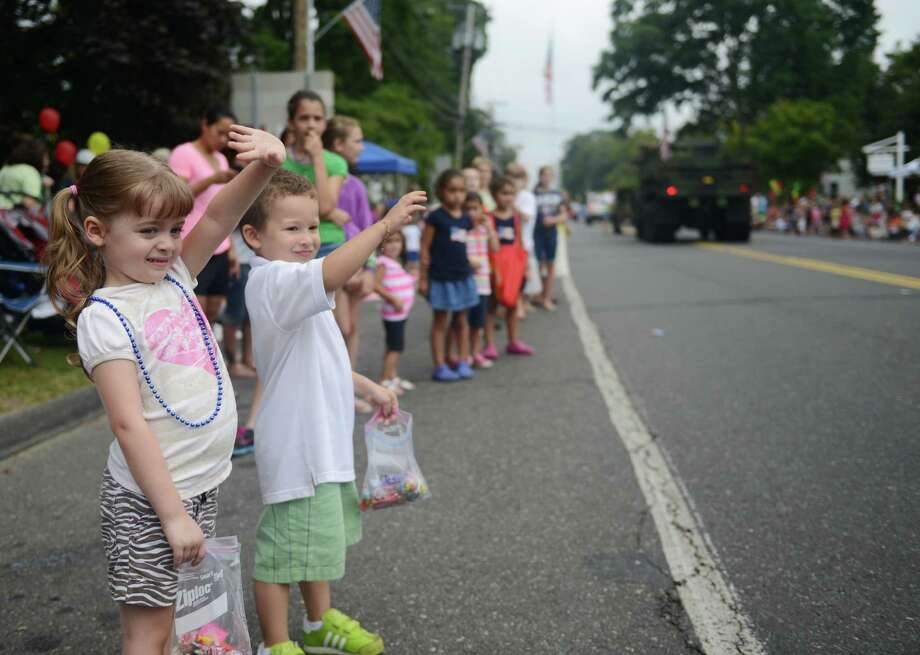 "Trinity Flick, 4, of Newtown, and Luke Solsbury, 4, of Naugatuck, wave at floats in the 52nd Annual Newtown Labor Day Parade in Newtown, Conn. on Monday, Sept. 2, 2013.  About 100 floats and groups participated in the parade, themed ""We are Newtown - marching strong."" Photo: Tyler Sizemore / The News-Times"
