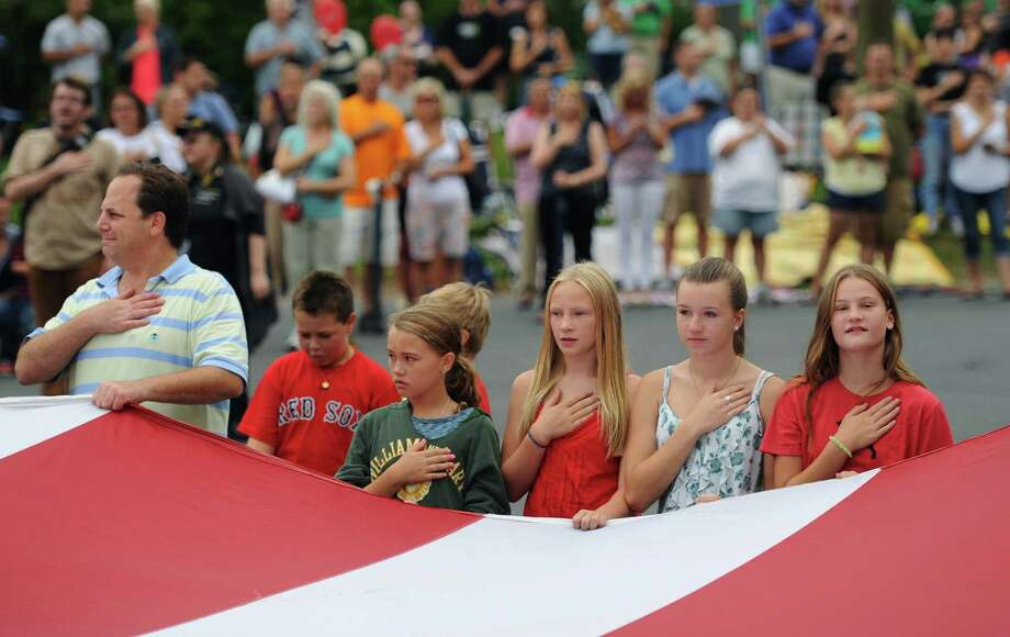 "Parade-goers put their hands over their hearts during the National Anthem while holding a giant, 90-foot-long American flag at the start of the 52nd Annual Newtown Labor Day Parade in Newtown, Conn. on Monday, Sept. 2, 2013.  About 100 floats and groups participated in the parade, themed ""We are Newtown - marching strong."" Photo: Tyler Sizemore / The News-Times"