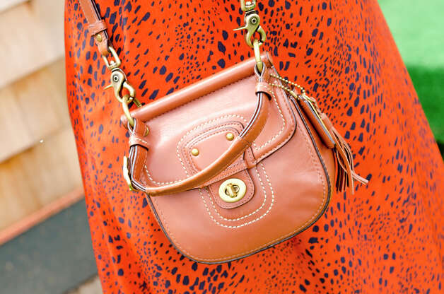 Sarah Schumacher, of New York, pairs a leather satchel by Coach, with her orange maxi dress at the Greenwich Polo Club on Sunday, Sept. 1, 2013. Photo: Amy Mortensen / Connecticut Post Freelance