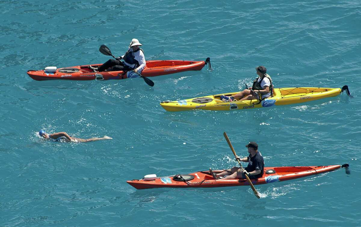 In this photo provided by the Florida Keys News Bureau, Diana Nyad, positioned about two miles off Key West, Fla., Monday, Sept. 2, 2013, is escorted by kayakers as she swims towards the completion of her approximately 110-mile trek from Cuba to the Florida Keys. Nyad, 64, is poised to be the first swimmer to cross the Florida Straits without the security of a shark cage. (AP Photo/Florida Keys News Bureau, Andy Newman) ORG XMIT: FLAN103