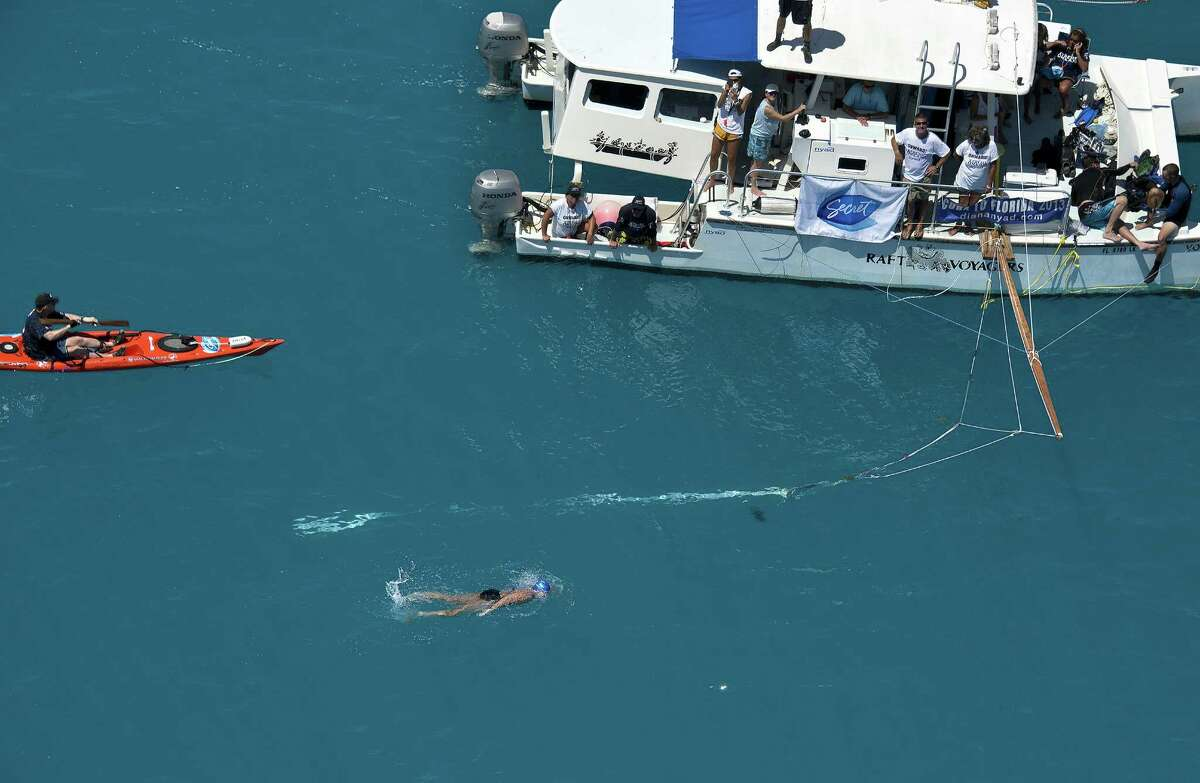 In this photo provided by the Florida Keys News Bureau, Diana Nyad, positioned about two miles off Key West, Fla., Monday, Sept. 2, 2013, swims towards the completion of her approximately 110-mile trek from Cuba to the Florida Keys. Nyad, 64, is the first swimmer to cross the Florida Straits without the security of a shark cage. (AP Photo/Florida Keys News Bureau, Andy Newman) ORG XMIT: FLAN102