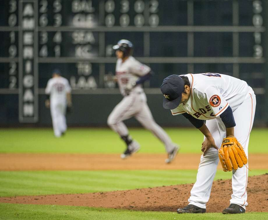 Relief pitcher Chia-Jen Lo hangs his head as Minnesota Twins first baseman Chris Colabello rounds the bases after hitting grand during the ninth inning. Photo: Smiley N. Pool, Chronicle