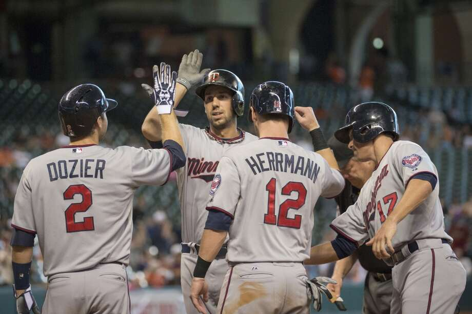 Twins first baseman Chris Colabello is greeted at home by Brian Dozier (2), Chris Herrmann (12) and Doug Bernier (17) after they all scored on his grand during the ninth inning. Photo: Smiley N. Pool, Chronicle