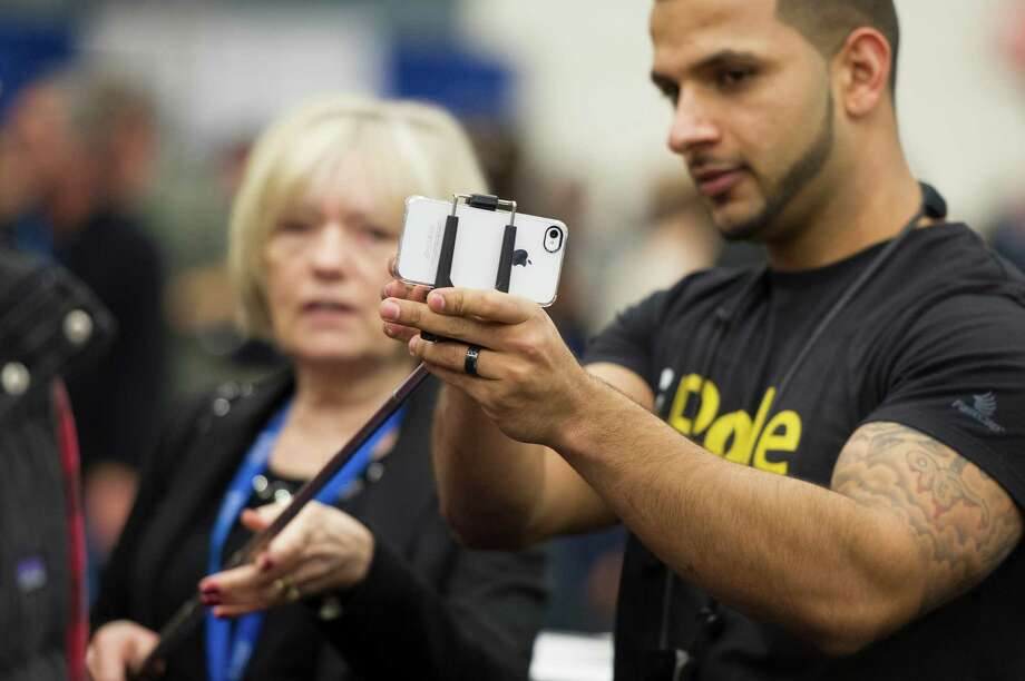 An attendee at MacWorld/iWorld early this year takes a photo with an iPhone. Apps for iPhones can add features or offer ways to improve photos. Photo: David Paul Morris / © 2013 Bloomberg Finance LP