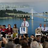 Steve Heminger, executive director of the Metropolitan Transportation Commission, speaks at the opening ceremony against a backdrop showing the Bay Bridge.