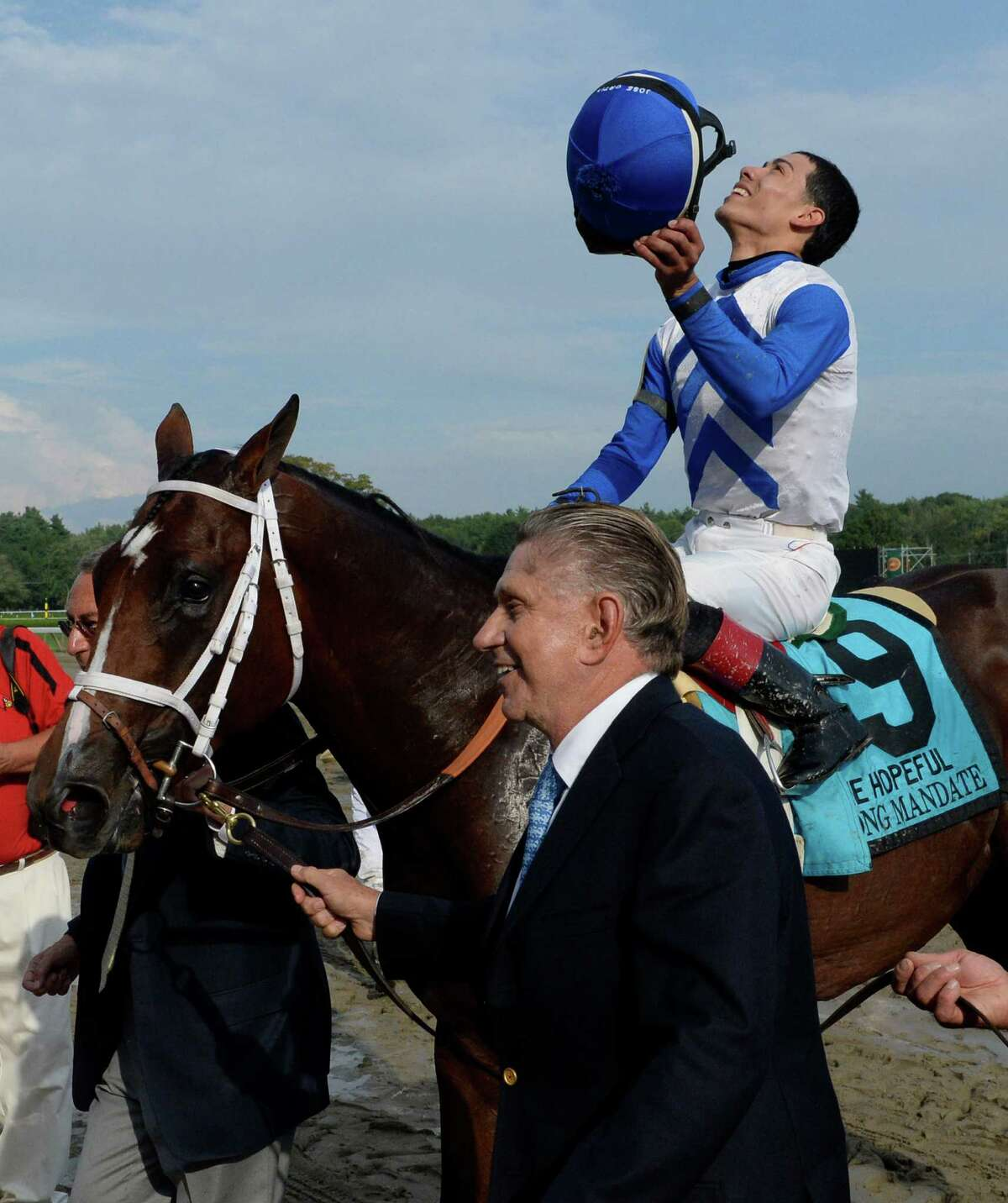 Jockey Jose Ortiz looks to the sky as he sits atop Strong Mandate while being led to the winner's circle by owner Bob Baker after winning the 109th running of The Hopeful Sept. 2, 2013, at the Saratoga Race Course in Saratoga Springs, N.Y. (Skip Dickstein/Times Union)