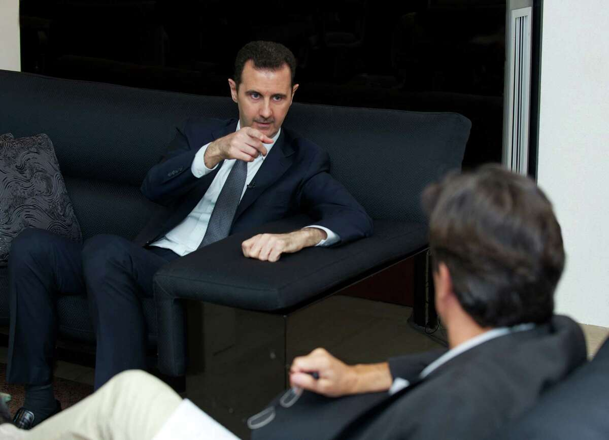 A handout picture released by the Syrian presidency media office and made on September 2, 2013 in Damas shows Syrian president Bashar al-Assad answering questions by French journalist Georges Malbrunot. Syrian leader Bashar al-Assad warned today that Western military strikes would risk igniting a