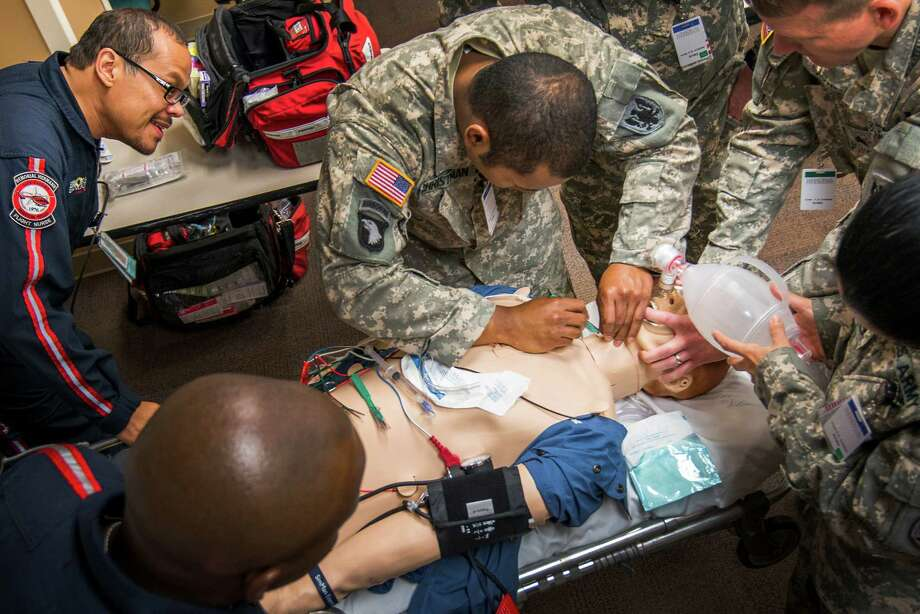 Under the watchful eye of Memorial Hermann Life Flight Flight Nurse Rudy Cabrera, left, Sgt. Marbou Christman practices a cricothyrotomy on a  high-fidelity mannequin. Another important teaching tool for the Army medics was being able to see the care an acute trauma patient receives beyond treatment in the air ambulance, Cabrera said. ÒKnowing all those aspects of patients and their injuries makes you more mindful of how to care for a patient,Ó he said. Photo: Smiley N. Pool, Houston Chronicle / © 2013  Houston Chronicle