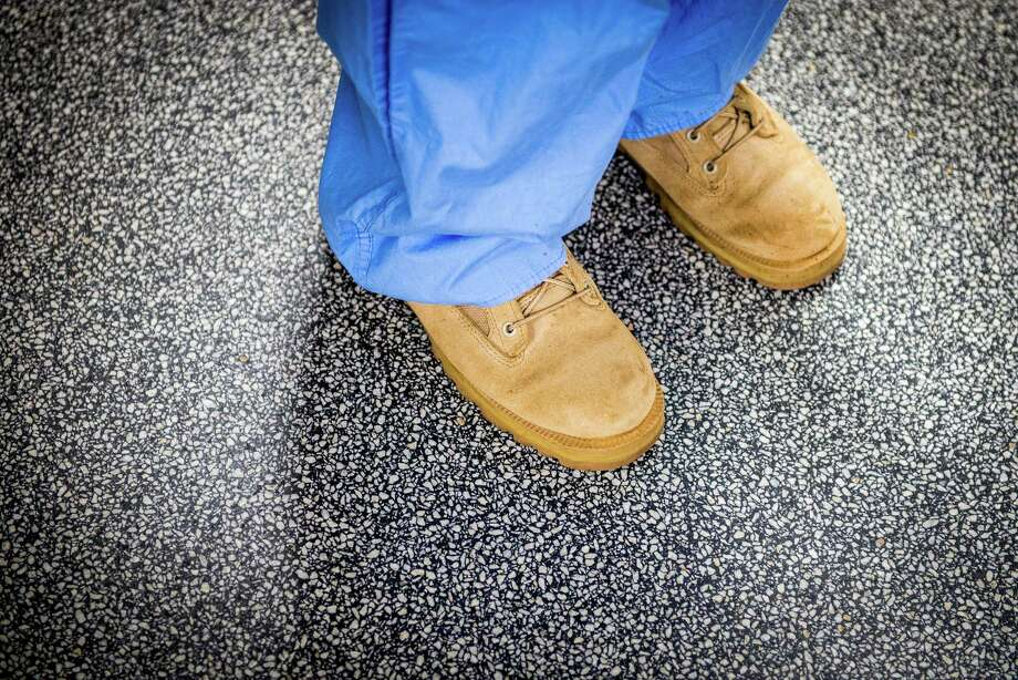 Wearing scrubs with her combat boots, Staff Sgt. Marie-Claire Glidden works in the Texas Trauma Institute. Photo: Smiley N. Pool, Houston Chronicle / © 2013  Houston Chronicle