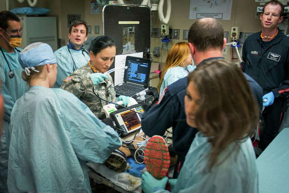 Staff Sgt. Marie-Claire Glidden assists with a with patient as they are brought into the emergency room. The program, an ongoing effort, grew out of an Army analysis of operations in Iraq and Afghanistan that showed advanced training of flight medics would improve patient outcomes. Photo: Smiley N. Pool, Houston Chronicle / © 2013  Houston Chronicle