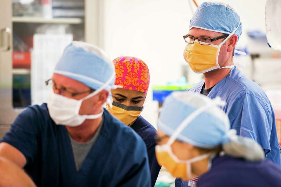 Sgt. Brian Etchison, right, observes the action in an operating room. ÒIÕm comfortable with the trauma stuffÓ said Etchison, who worked as a police officer in Nashville, Tenn. ÒItÕs the medical stuff, like if someone is sick and how to fix them, that I needed.Ó Photo: Smiley N. Pool, Houston Chronicle / © 2013  Houston Chronicle