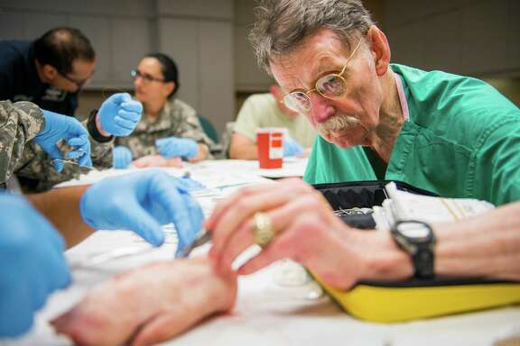 "Using pigs' feet, Dr. James ""Red"" Duke instructs a group of Army flight medics on proper suturing techniques at Memorial Hermann Hospital."