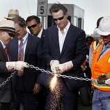 Lt. Governor Gavin Newsom did the honors with a torch to open the bridge Monday September 2, 2013. The celebration for the opening of the eastern span of the Bay Bridge began with a ceremony in the Bridge Yard building near the toll plaza, followed by a chain cutting ceremony nearby.
