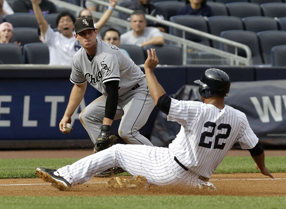 New York Yankees' Vernon Wells, bottom, slides safely into third while Chicago White Sox third baseman Conor Gillaspie looks on during the fourth inning of the baseball game at Yankee Stadium Monday, Sept. 2, 2013 in New York. (AP Photo/Seth Wenig) ORG XMIT: NYY108