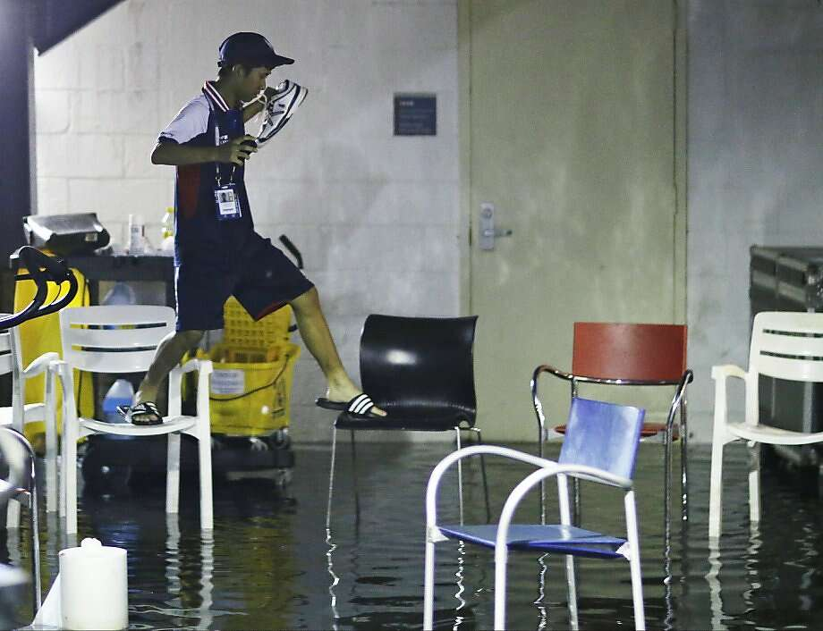 A ball boy chair hops over a flooded area between Grandstand and Louis Armstrong stadiums during a rain delay in the fourth round of the 2013 U.S. Open tennis tournament, Monday, Sept. 2, 2013, in New York.  Photo: David Goldman, Associated Press